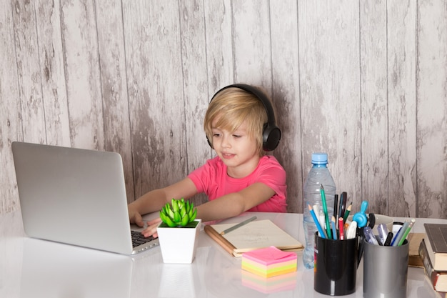 Menino bonito criança em fones de ouvido de camiseta rosa preto usando laptop cinza em cima da mesa junto com canetas de garrafa de planta verde na parede cinza Foto gratuita
