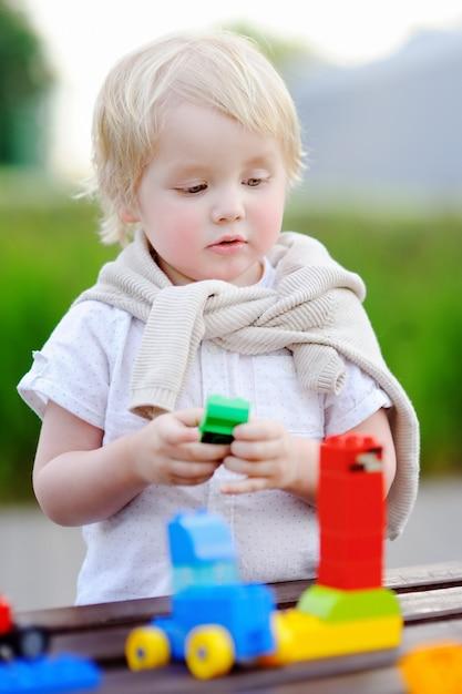 Menino bonito da criança brincando com trem de brinquedo e blocos de plástico coloridos ao ar livre em dia quente Foto Premium