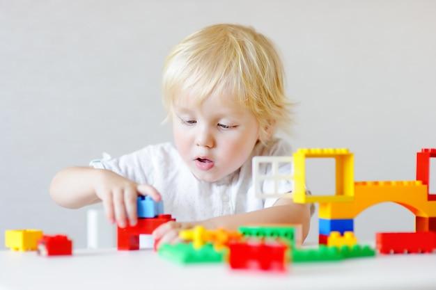 Menino bonito da criança brincar com blocos de plástico coloridos dentro de casa Foto Premium