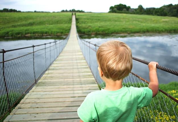 Menino bonito da criança em uma ponte de suspensão através do rio. viagem de aventura, olhe para o futuro, abrindo um novo conceito de caminho Foto Premium