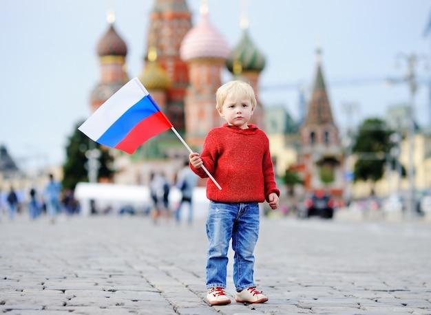 Menino bonito da criança segurando a bandeira russa com a red square e vasilevsky descida Foto Premium