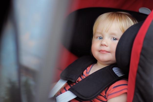 Menino bonito da criança sentada no banco do carro Foto Premium