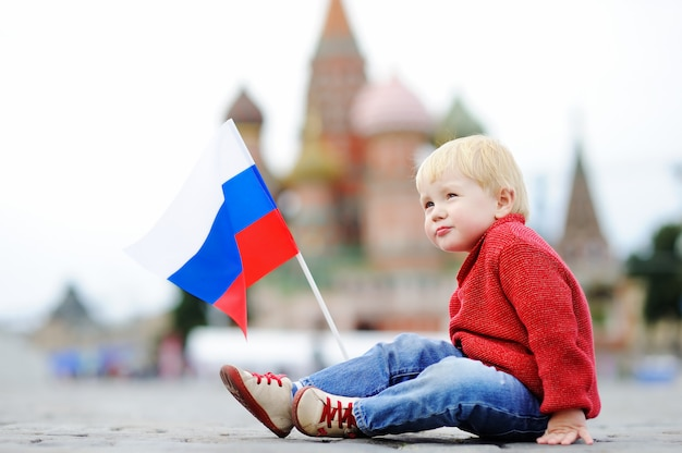 Menino bonito da criança sentado e jogando com a bandeira russa com a red square e vasilevsky descida Foto Premium