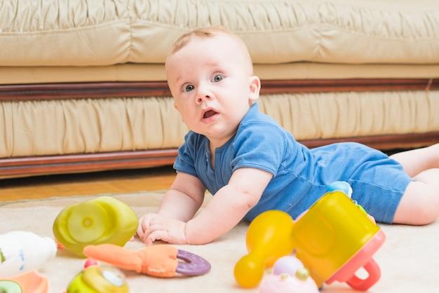 Menino bonito, deitado no tapete com brinquedos Foto gratuita