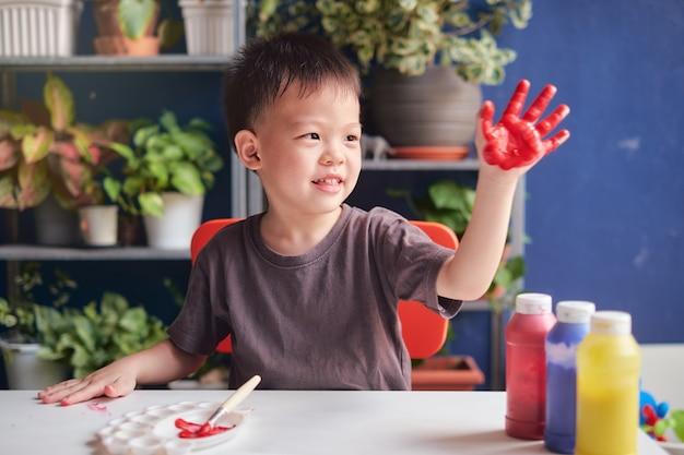 Menino bonito do jardim de infância asiático de 4 anos pintando a dedo com as mãos e aquarelas Foto Premium