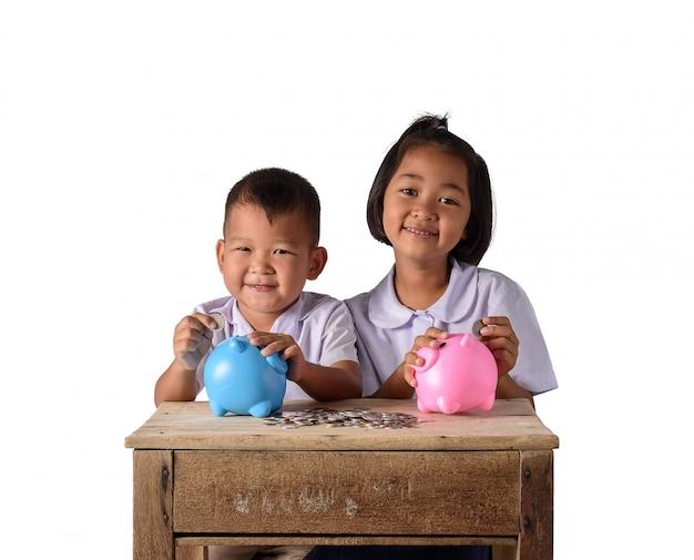 Menino bonito do país asiático e menina colocando moedas no cofrinho isolado no fundo branco Foto Premium