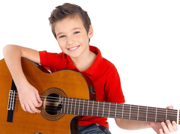 Menino bonito e feliz tocando violão isolado no branco Foto gratuita
