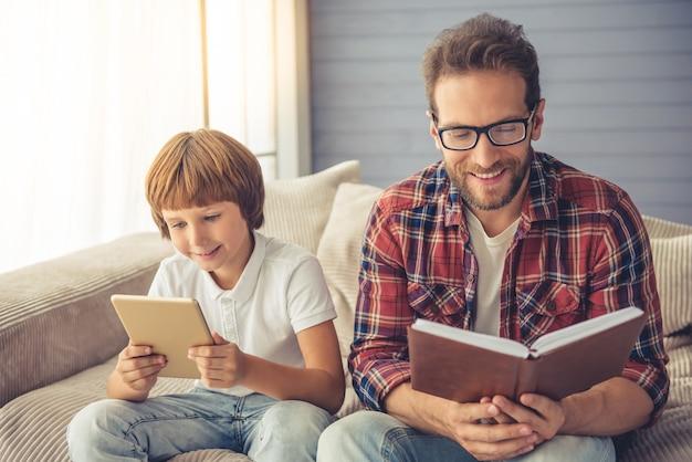 Menino bonito está usando um tablet digital em casa. Foto Premium