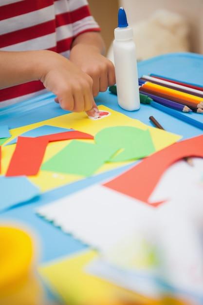 Menino bonito fazendo arte na sala de aula Foto Premium