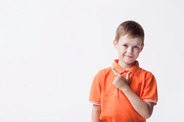 Menino bonito gesticulando e olhando para a câmera Foto Premium