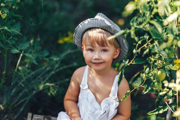 Menino bonito no chapéu e roupas casuais, sentado em torno de ang tomates olhando para a câmera Foto Premium