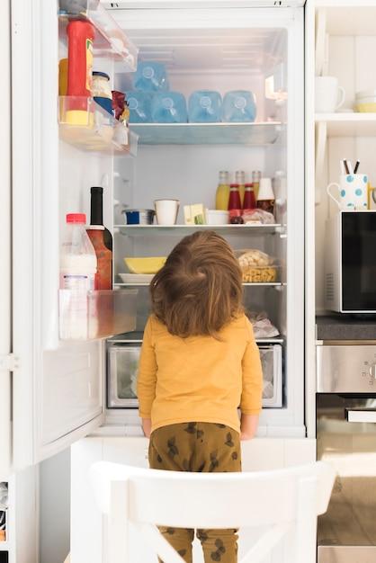Menino bonito, olhando para a geladeira alta Foto gratuita