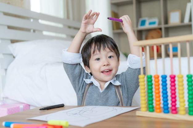 Menino bonito orgulhoso quando ele termina de desenhar com felicidade, levantou as duas mãos sobre a cabeça e sorri Foto gratuita