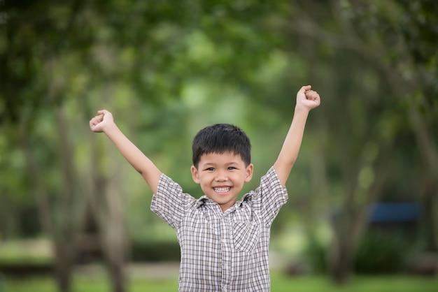 Menino bonito pequeno que aprecia levantando as mãos com natureza sobre o fundo borrado da natureza. Foto gratuita