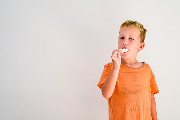 Menino bonito que come um gelado no fundo branco. Foto Premium