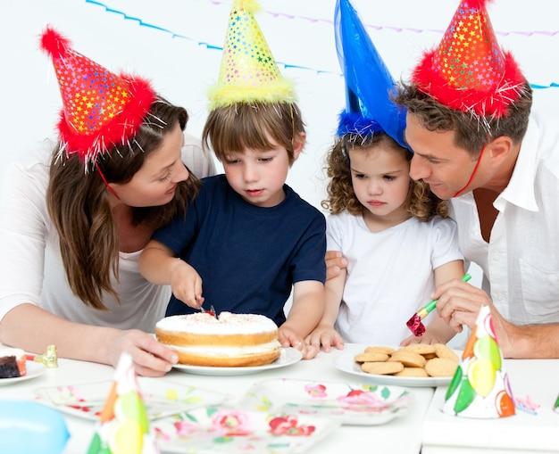 Menino bonito que corta um bolo de aniversário para sua família Foto Premium