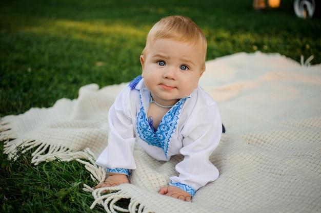Menino bonito, vestido com a camisa bordada, deitado sobre a manta na grama verde Foto Premium