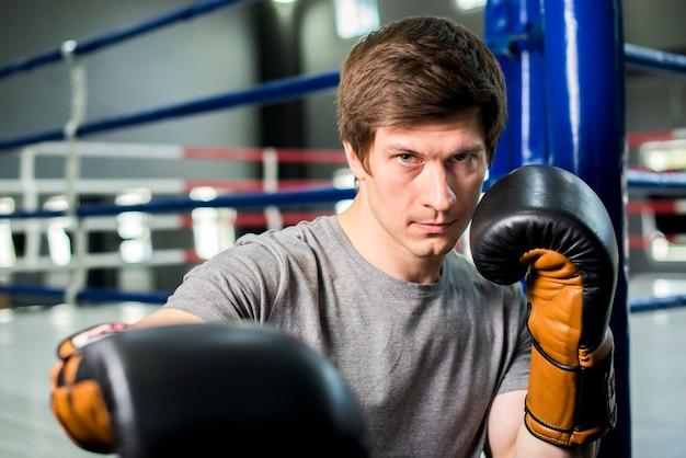 Menino boxer posando no ginásio Foto gratuita