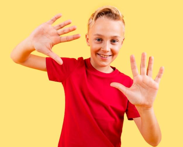 Menino brincalhão, mostrando as duas mãos no humor livre Foto gratuita