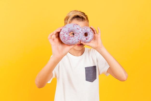 Menino brincalhão segurando rosquinhas Foto gratuita