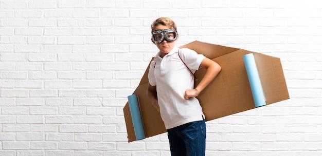 Menino brincando com asas de avião de papelão posando com os braços no quadril Foto Premium
