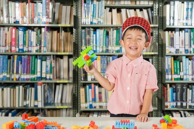 Menino brincando com blocos de plástico na escola da sala da biblioteca Foto gratuita