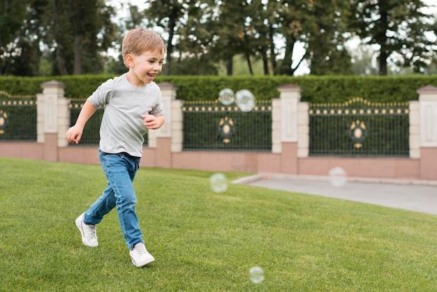 Menino brincando com bolhas de sabão Foto gratuita