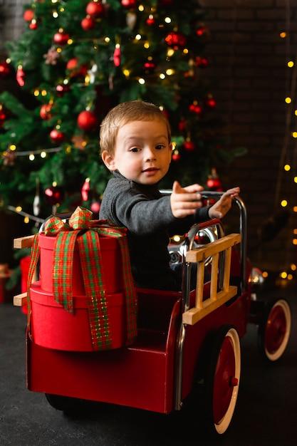 Menino brincando com brinquedos de natal Foto Premium