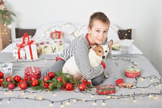 Menino brincando com cachorro jack russell em uma cama com decoração de ano novo Foto Premium