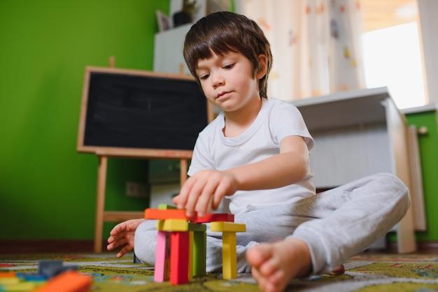 Menino brincando com cubos de madeira, brinquedos no berçário em casa ou na creche Foto Premium