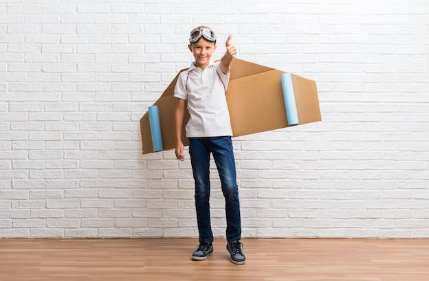 Menino brincando com papelão avião asas nas costas dando um polegar para cima gesto e sorrindo Foto Premium