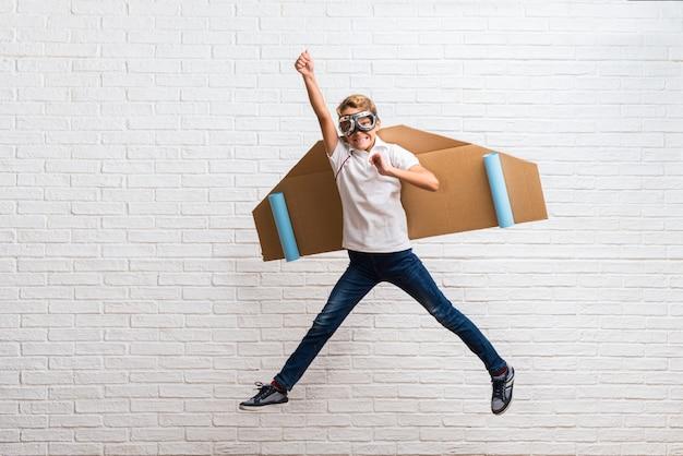 Menino brincando com papelão avião asas pulando Foto Premium