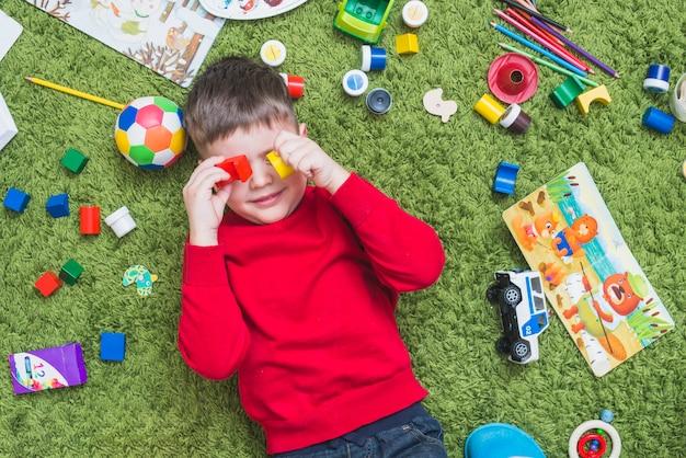 Menino, brinquedos jogando, ligado, chão Foto gratuita