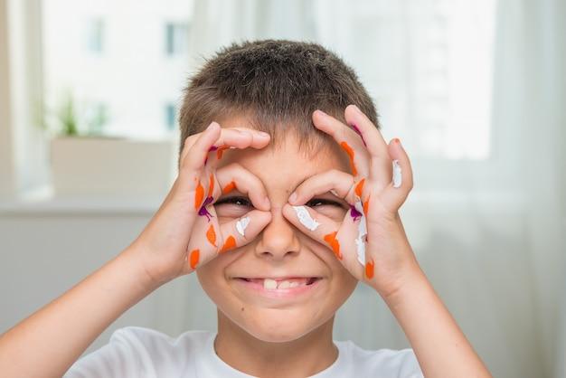 Menino caucasiano feliz com mãos pintadas, artista alegre, foco seletivo. Foto Premium