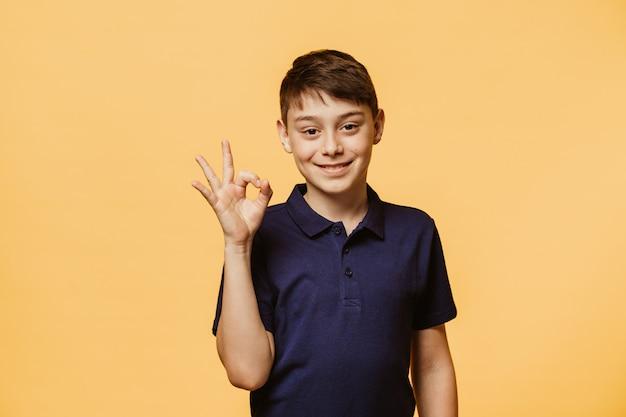Menino caucasiano positivo mostra sinal de ok, demonstra que está tudo bem, concorda com as pessoas que o rodeiam. rapaz alegre confiante gestos dentro de casa. linguagem corporal e o conceito de emoções humanas Foto Premium