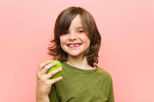 Menino caucasiano, segurando uma maçã Foto Premium