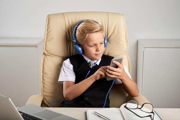 Menino caucasiano, sentado na mesa executiva no escritório, com fones de ouvido e smartphone Foto gratuita
