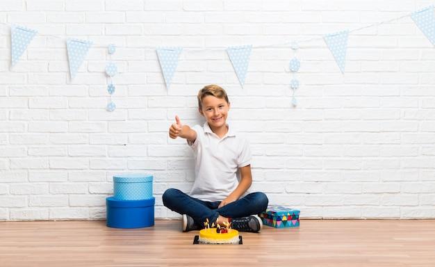 Menino, celebrando, seu, aniversário, com, um, bolo, dar, um, polegares cima, gesto, e, sorrindo Foto Premium