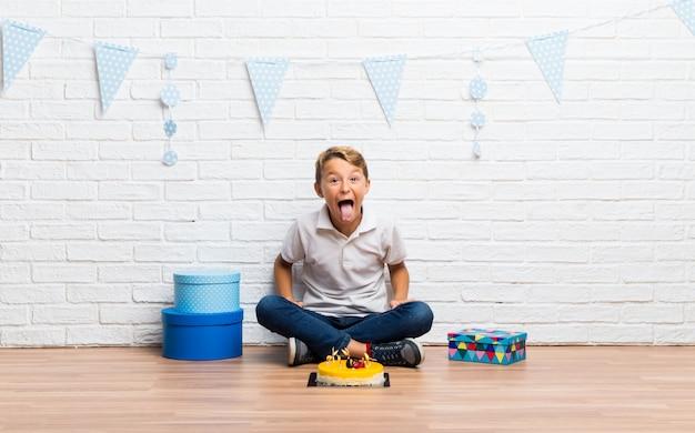 Menino, celebrando, seu, aniversário, com, um, bolo, mostrando, língua, câmera, tendo, engraçado, olhar Foto Premium