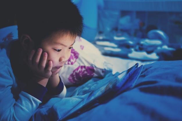 Menino chinês asiático jogando smartphone na cama, garoto usar telefone e jogar o jogo Foto Premium