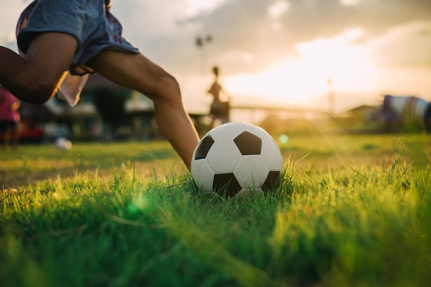 Menino chutando uma bola com o pé descalço enquanto jogava futebol de rua no campo de grama verde Foto Premium