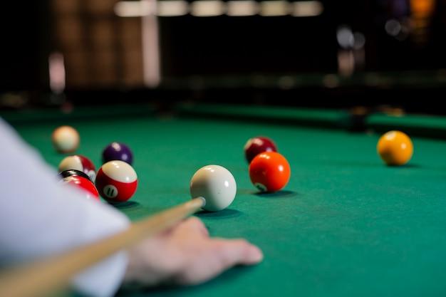 Menino close-up com taco de bilhar jogando bilhar Foto gratuita