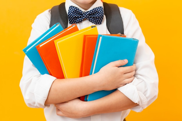 Menino close-up, segurando livros Foto gratuita