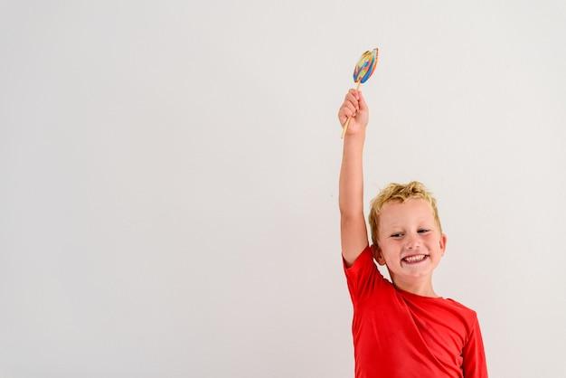 Menino com a camisa vermelha no fundo branco que come um divertimento colorido e um riso do pirulito. Foto Premium