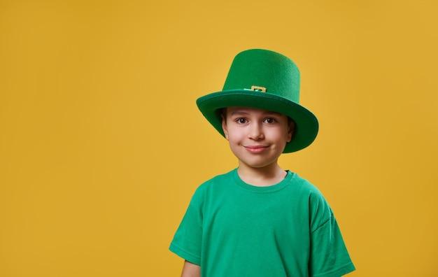 Menino com camiseta verde e boné irlandês de duende olhando para a câmera Foto Premium