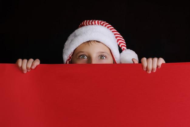 Menino com chapéu de papai noel segurando a faixa vermelha em branco para os cumprimentos de natal. isolado no preto Foto Premium