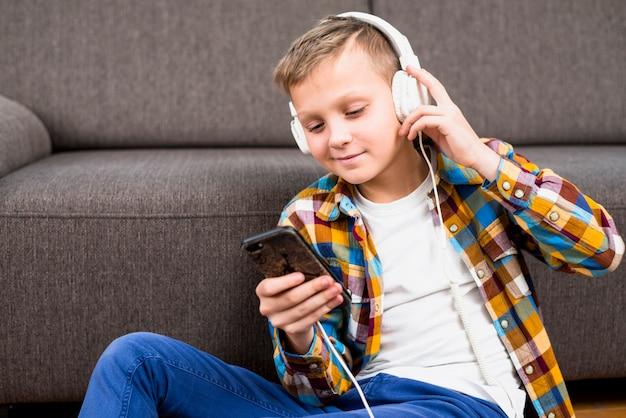 Menino, com, fones, usando, smartphone Foto gratuita