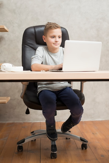 Menino, com, laptop, em, escritório Foto gratuita