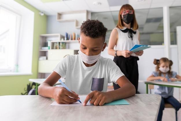 Menino com máscara médica escrevendo Foto Premium