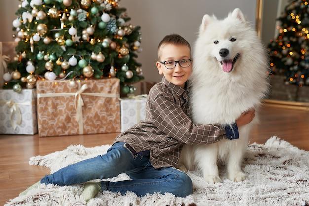 Menino com o cão perto da árvore de natal no fundo do natal Foto Premium